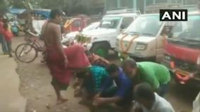 a-temple-priest-gives-blessings-to-people-by-putting-his-foot-on-their-heads